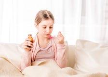 Menina adolescente que toma o xarope para curar-se imagem de stock royalty free