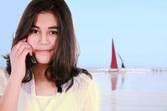 Menina adolescente que usa o telefone de pilha na praia Foto de Stock