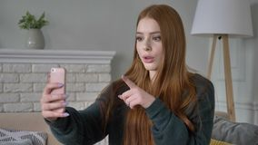 A menina adolescente ruivo bonita nova usa um smartphone, bate-papo video, conforto home no fundo 60 fps filme
