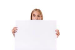 Menina adolescente surpreendida atrás da placa vazia, isolada Fotos de Stock