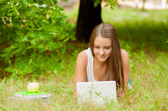 A menina adolescente trabalha com o portátil na grama Imagens de Stock Royalty Free