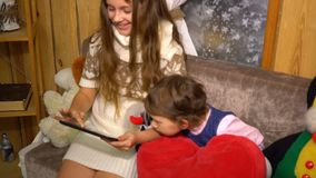 A menina adolescente usa a tabuleta com irmã mais nova em casa vídeos de arquivo