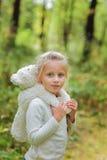 A menina adorável abraça seu brinquedo macio favorito em um dia de verão no parque Foto de Stock