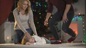Menina adorável adormecidos caído sob a árvore X-mas, pais felizes que vêm e que afagam filme