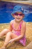 A menina adorável com óculos de sol cor-de-rosa e o chapéu azul sentam-se na associação em s Imagens de Stock