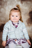 Menina adorável com o cabelo louro que senta-se na cadeira branca Foto de Stock