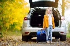 Menina adorável com uma mala de viagem pronta para ir em férias com seus pais Criança que olha para a frente para uma viagem por  Imagem de Stock