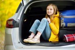 Menina adorável com uma mala de viagem pronta para ir em férias com seus pais Criança que olha para a frente para uma viagem por  Foto de Stock Royalty Free