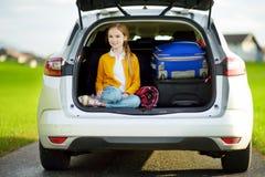 Menina adorável com uma mala de viagem pronta para ir em férias com seus pais Criança que olha para a frente para uma viagem por  Fotografia de Stock Royalty Free