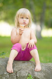 A menina adorável come o gelado que senta-se na pedra Foto de Stock
