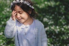 Menina adorável da criança da criança na luz - equipamento elegante azul que anda e que joga no jardim de florescência da mola Foto de Stock Royalty Free