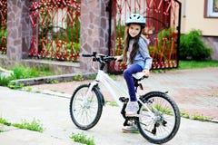 Menina adorável da criança no capacete azul que monta sua bicicleta Fotos de Stock