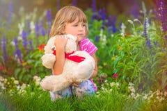 Menina adorável da criança que abraça seu urso de peluche favorito imagem de stock