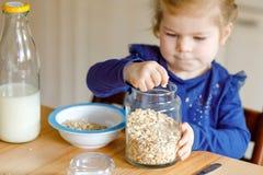Menina adorável da criança que come farinhas de aveia saudáveis com leite para a criança feliz bonito do bebê do café da manhã no foto de stock royalty free
