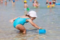 Menina adorável da criança que joga com brinquedos da praia foto de stock