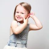 Menina adorável de sorriso que penteia seu cabelo Foto de Stock Royalty Free