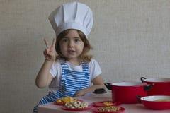 Menina adorável do retrato no alimento do cozinheiro do chapéu do cozinheiro chefe mostra aos dedos uma vitória Foto de Stock Royalty Free