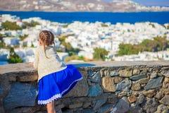 Menina adorável em opinião surpreendente do fundo da cidade de Mykonos de casas brancas tradicionais Fotografia de Stock Royalty Free