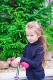 Menina adorável em um 'trotinette' na jarda Foto de Stock Royalty Free