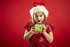 Menina adorável em um vestido do Natal no chapéu de uma Santa com um presente do Natal fotos de stock royalty free