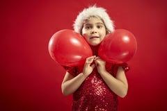 Menina adorável em um vestido do Natal no chapéu de uma Santa com um presente do Natal imagens de stock
