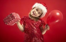 Menina adorável em um vestido do Natal no chapéu de uma Santa que guarda um presente fotos de stock