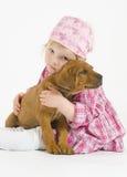 A menina adorável está abraçando seu filhote de cachorro pequeno fotos de stock