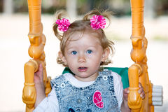 Menina adorável feliz da criança no balanço no campo de jogos perto do jardim de infância Montessori no verão Fotos de Stock Royalty Free