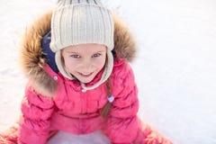 Menina adorável feliz que senta-se no gelo com patins Fotografia de Stock