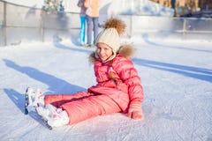 Menina adorável feliz que senta-se no gelo com patins Fotografia de Stock Royalty Free