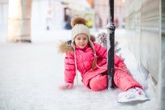 Menina adorável feliz que senta-se no gelo com patins Imagens de Stock