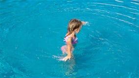 Menina adorável na piscina exterior filme