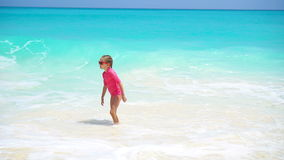 Menina adorável na praia que tem muito divertimento na água vídeos de arquivo