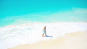 Menina adorável na praia que tem muito divertimento na água pouco profunda filme