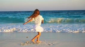 Menina adorável na praia que tem muito divertimento na água pouco profunda Movimento lento video estoque