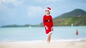 Menina adorável no chapéu do Natal na praia branca durante férias do Xmas vídeos de arquivo