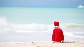 Menina adorável no chapéu do Natal na praia branca durante férias do Xmas filme