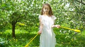 Menina adorável no jardim de florescência da maçã no dia de mola bonito video estoque