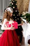 Menina adorável no vestido da princesa com a caixa de presente perto do abeto tr Fotografia de Stock Royalty Free