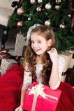 Menina adorável no vestido da princesa com a caixa de presente perto do abeto tr Imagens de Stock Royalty Free