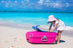 Menina adorável pequena com a mala de viagem colorida grande e um mapa nas mãos na praia tropical Fotografia de Stock Royalty Free