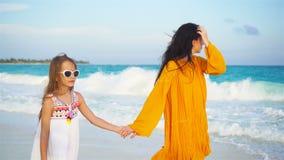Menina adorável pequena e mãe nova na praia tropical video estoque