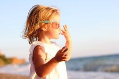 Menina adorável pequena em uma praia perto de um mar imagens de stock royalty free