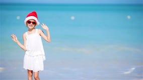 Menina adorável pequena no chapéu do Natal na praia branca durante férias do Xmas Criança de sorriso feliz que olha a câmera filme