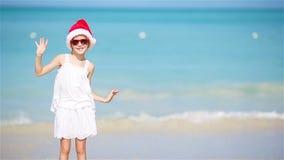Menina adorável pequena no chapéu do Natal na praia branca que tem o divertimento em férias do Xmas vídeos de arquivo