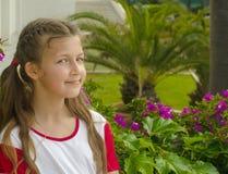 Menina adorável pequena que cheira flores coloridas no dia de verão foto de stock