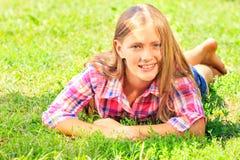 Menina adorável pequena que encontra-se na grama Fotos de Stock Royalty Free