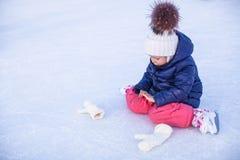 Menina adorável pequena que senta-se no gelo com patins Imagens de Stock Royalty Free