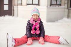 Menina adorável pequena que senta-se no gelo com patins Fotos de Stock Royalty Free