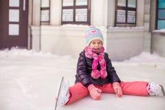 Menina adorável pequena que senta-se no gelo com patins Fotografia de Stock Royalty Free